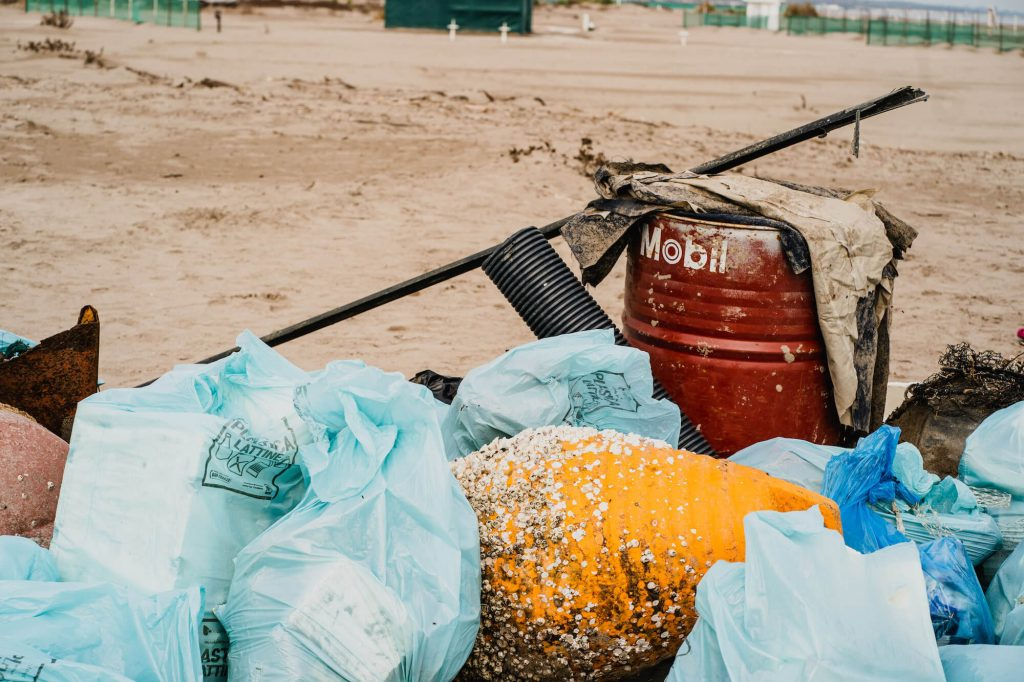 trash bags filled with plastic debris and mix waste materials beach clean up marina porto caleri